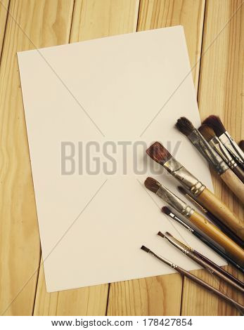 Brush And Sheet Of Paper On A Wooden Bg