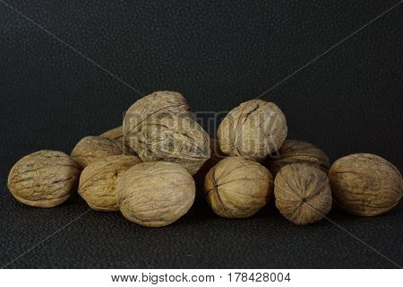 Walnuts in shell are stacked on a dark background. Healthy eating good for the brain.