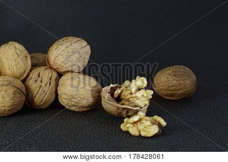 Walnuts lie in a heap on a dark background one is split half the shell and a delicious kernel. Healthy eating good for the brain