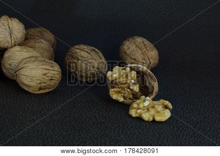 Walnuts lie in a heap on a dark background one is split half the shell and a kernel. Healthy eating good for the brain