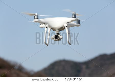 KAGAWA, JAPAN - MARCH 17, 2017: White remote controlled Drone Dji Phantom4 Pro equipped with high resolution video camera hovering in air and blue sky in the background