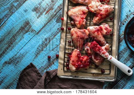 Close up raw chicken wings in cranberry sauce on a baking tray on a blue wooden table with copy space top view. Tasty and healthy food