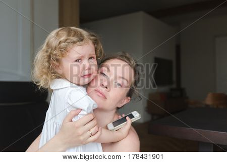 Woman and little crying girl holding phone looking at camera. Horizontal indoors shot.