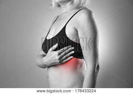 Breast test woman examining her breasts for cancer heart attack pain in human body black and white photo with red spots