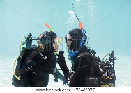 Man proposing marriage to the shocked woman underwater in scuba gear