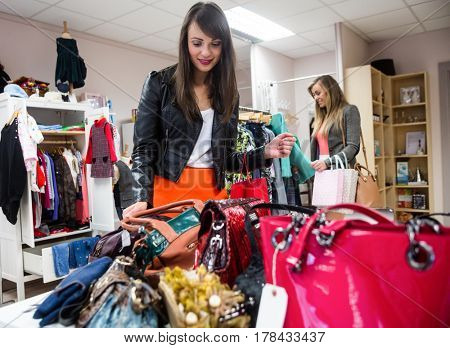 Women selecting bags and shoes while shopping in mall