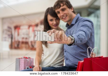 Couple taking a selfie on mobile phone in shopping mall