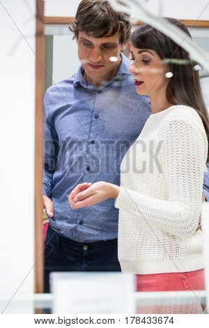 Couple standing together and talking in shop