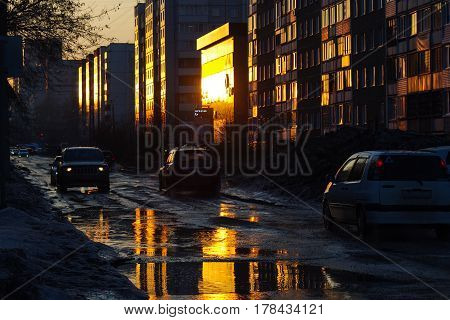 cars on a city street on the rays of a sunset reflected in spring puddles