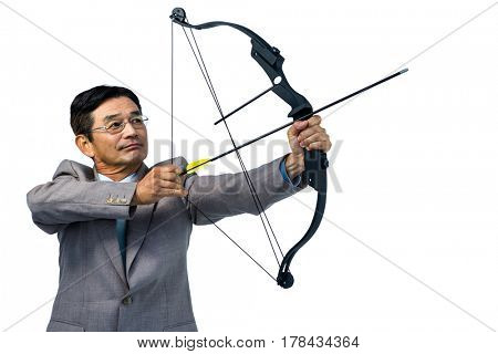 Focused businessman shooting a bow and arrow on white background
