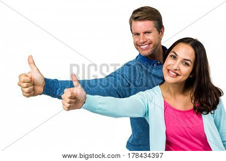 Portrait of smiling couple showing thumps up sign against white background
