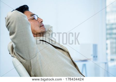 Smiling asian businessman stretching in office