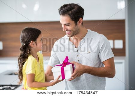 Smiling daughter giving gift box to father at home