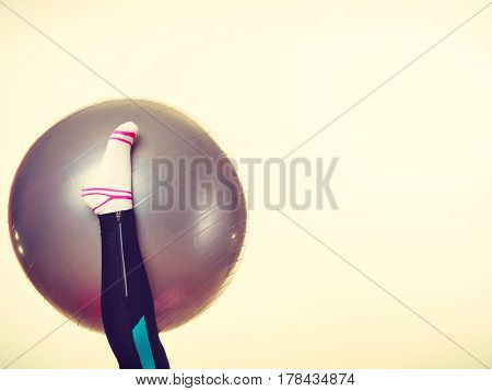 Sport people gym fitness concept. Girl foot with fit ball. Lady wearing a sock and leggins.