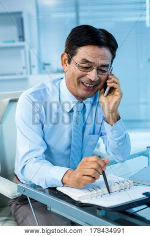 Smiling asian businessman calling someone in office