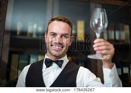 Portrait of waiter holding wine glass in a fancy restaurant
