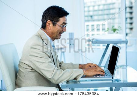 Smiling asian businessman working on laptop in office