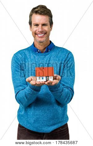 Portrait of smiling man holding model house against white background