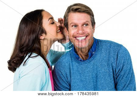 Woman sharing secret with man against white background