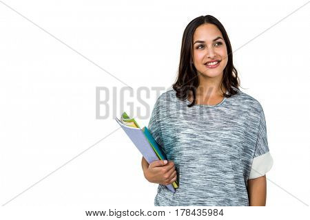 Woman holding books while looking away against white background