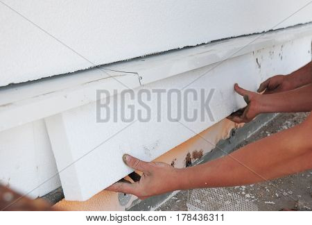 Contractor insulating foundation with hands and polystyrene foam boards for House Energy Saving. Foundation Insulation.