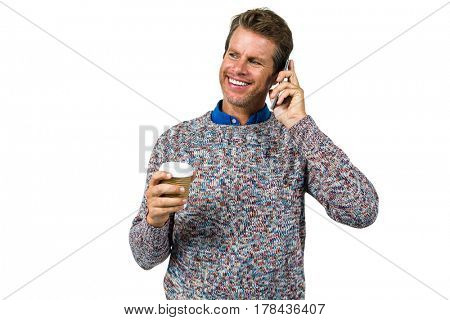 Smiling man holding coffee while talking on phone against white background