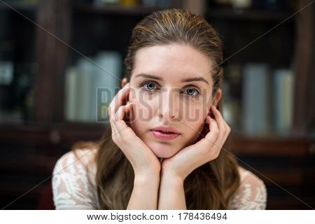 Portrait of sad woman with hand on chin at restaurant