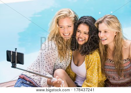 Beautiful women taking a selfie by swimming pool on a sunny day