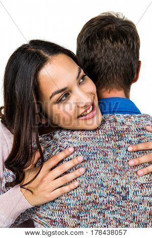 Close-up of woman hugging man against white background