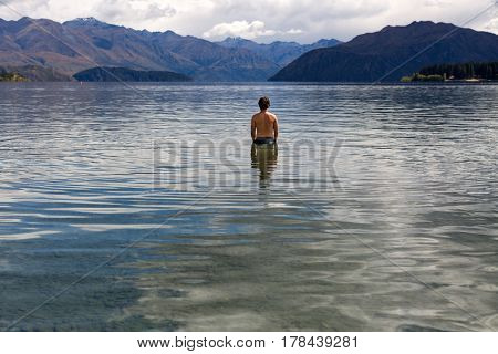 Man standing in still remote lake