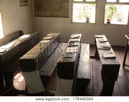 A nostalgic look at the benches and tables in an old classroom with windows and pot