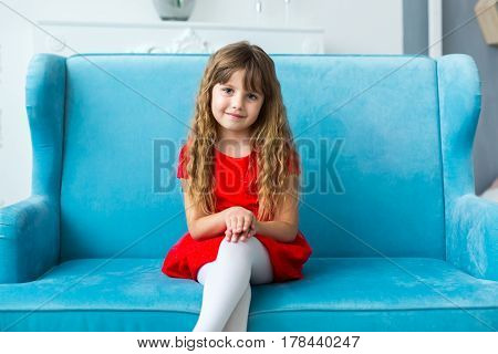 Young girl in a red dress sitting on a blue couch and posing.