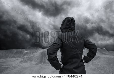 Youth lifestyle concept unrecognizable hooded person standing in empty futuristic skateboarding park dramatic sky in background for uncertain and unpredictable future