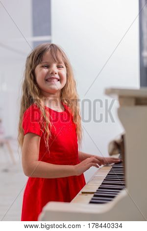 Young girl in a red dress plays the piano.