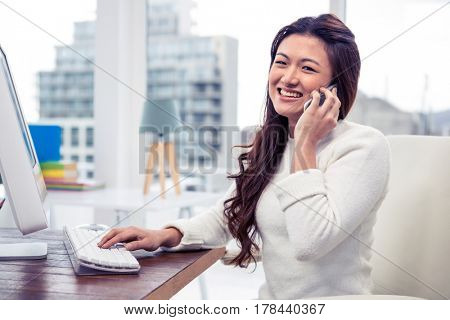 Smiling businesswoman on phone call in office