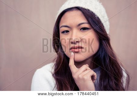 Thoughtful Asian woman with finger on chin