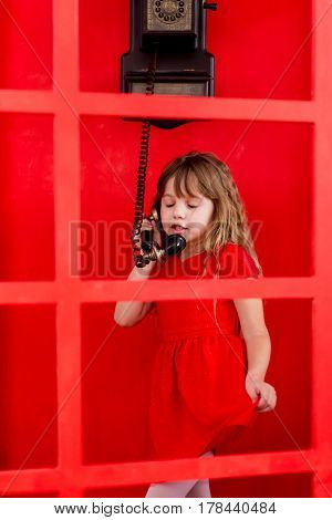 Young girl speaking on the telephone in red cabin.