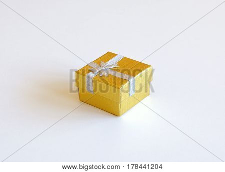 Still life with golden gift box with ribbon isolated on white background