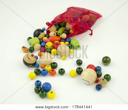 Still life with colorful wooden beads spill from organza bag isolated on white background