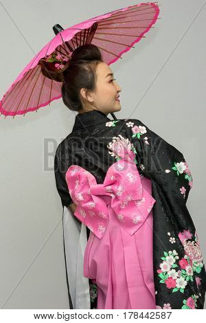 beautiful geisha standing back and turning in traditional japanese kimono with parasol