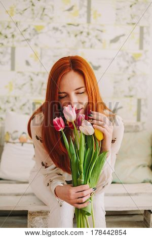 red-haired girl sniffing a bouquet of tulips