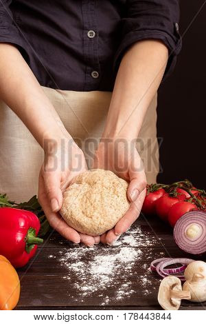Woman Preparing Dough For Pizza. Hands Holding Dough In The Kitchen.