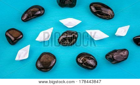 White paper boats in sigle file between abstract rock stones on blue background. Shot from Top Perspective.