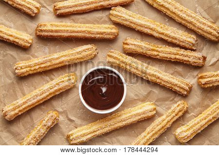 Churros traditional homemade Spain street fast food baked sweet dough snack dessert with chocolate on rustic decorative parchment paper background. Flat lay top view