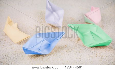 Coloured Paper Ships Chaotic Laying on Sandy in the Desert.