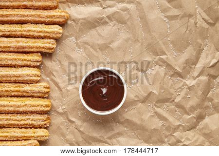 Churros traditional Spain breakfast or lunch street fast food baked sweet dough snack dessert with chocolate dipping on rustic decorative parchment paper background. Flat lay top view
