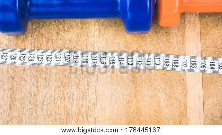 Blue and orange dumbbells and centimetric tape in front on wooden surface.