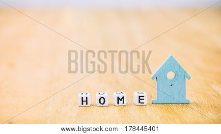 HOME Sweet horizontal word of cube letters behind blue house symbol on wooden surface