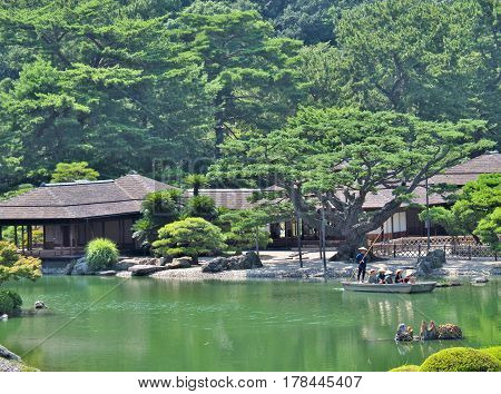 Kagawa, Japan - July 22, 2016: Tourists on the boat in Ritsurin Garden in Takamatsu city, Kagawa Prefecture, Japan. Ritsurin Garden is one of the most famous historical gardens in Japan.