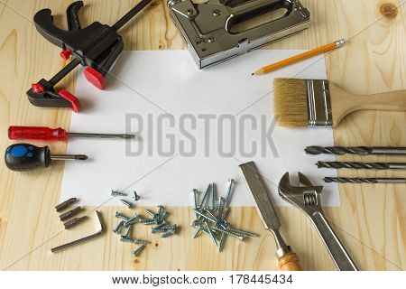 Tools for repairs in the house on a wooden table. Screws screwdrivers clamps